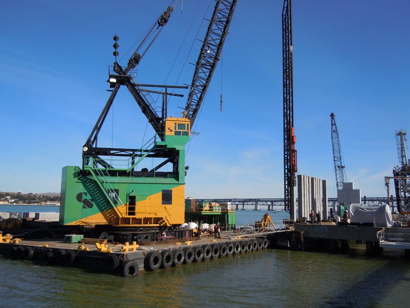 Floating crane pile driving.